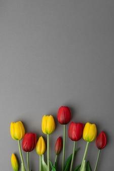 Tulipani gialli e rossi su superficie grigia