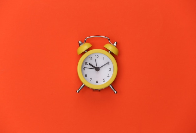 Sveglia retrò gialla su sfondo arancione brillante. . minimalismo