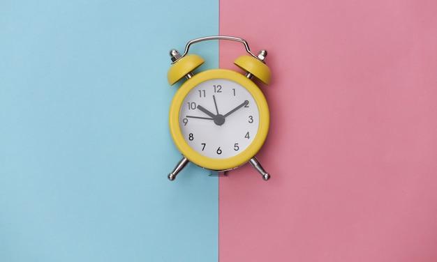 Sveglia retrò gialla su sfondo rosa pastello blu. . minimalismo