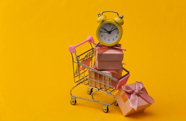 Sveglia retrò gialla e pila di scatole regalo nel carrello del supermercato su sfondo giallo.