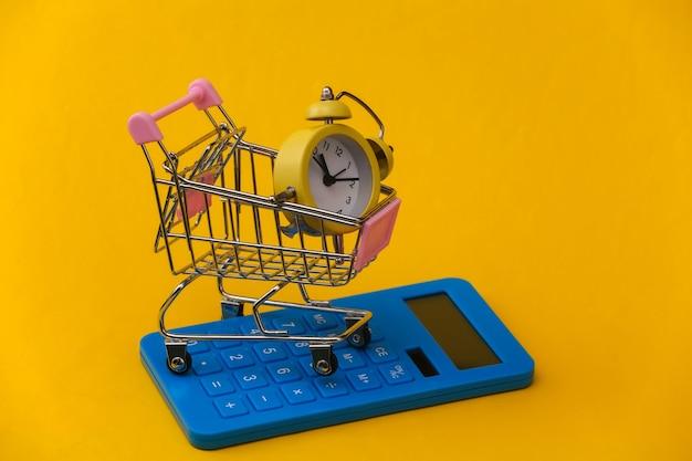Sveglia retrò gialla nel carrello del supermercato e calcolatrice su sfondo giallo. risparmi, spese di acquisto