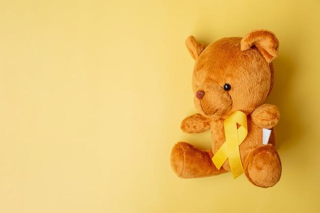 Nastro giallo con bambola orso su sfondo giallo per sostenere la vita e la malattia dei bambini. settembre childhood cancer awareness month e concetto di giornata mondiale del cancro