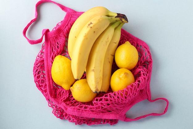 Banane e limoni maturi gialli in borsa a rete di colori fucsia su sfondo chiaro