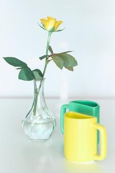 Fiore di rosa gialla, due tazze da tè in giallo brillante e verde menta. design minimalista per la tua casa in colori vivaci. arredamento moderno, regali romantici. design per biglietto di auguri o poster.