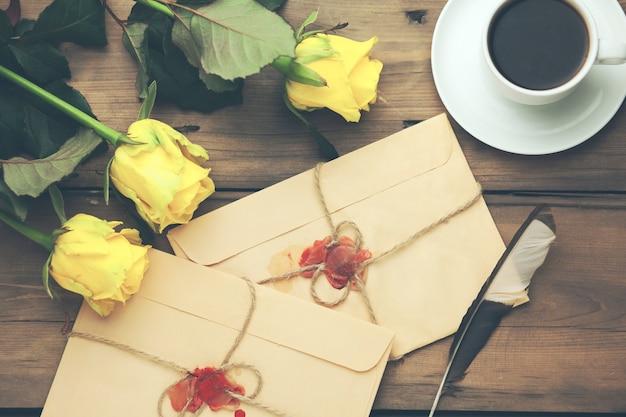 Rosa gialla con lettere e caffè sul tavolo