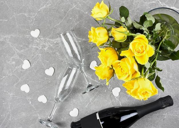 Rose gialle, bottiglia di spumante, flûte da champagne e cuori bianchi su grigio