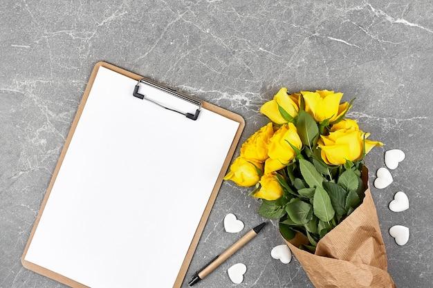 Rose gialle in carta artigianale e cartella appunti su grigio