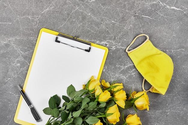Rose gialle, maschera protettiva gialla e cartella per appunti su grigio