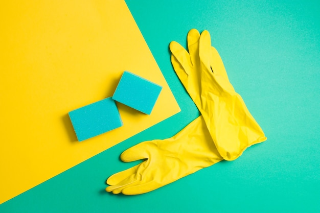 Guanti di gomma gialli e spugne per lavare i piatti su una superficie verde e gialla