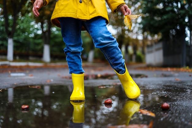 Scarpe di gomma gialle nella pozzanghera dopo la pioggia. foglie cadenti. concetto di stagione autunnale.
