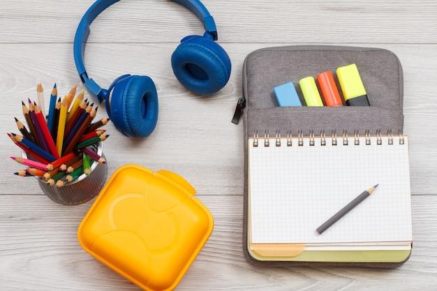 Scatola di panini gialla supporto in metallo con matite colorate, cuffie e quaderno aperto