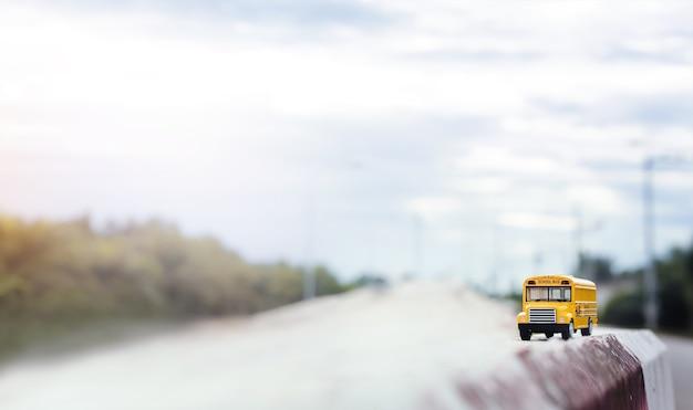 Modello giallo del giocattolo dello scuolabus sulla strada campestre. ritorno a scuola, istruzione e priorità bassa di concetto di trasporto.
