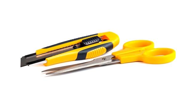 Forbici gialle e coltello da taglio isolato su sfondo bianco.