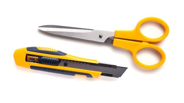 Forbici gialle e coltello da taglio isolato su bianco.