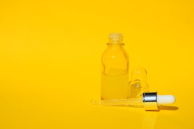 Olio liquido di siero giallo in flacone trasparente con contagocce