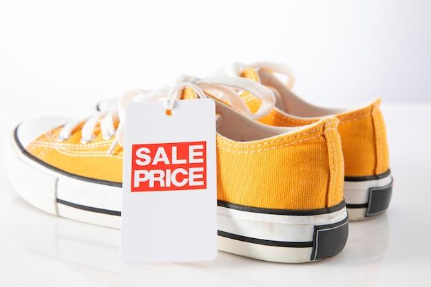 Scarpe gialle con vendita etichetta rossa su bianco