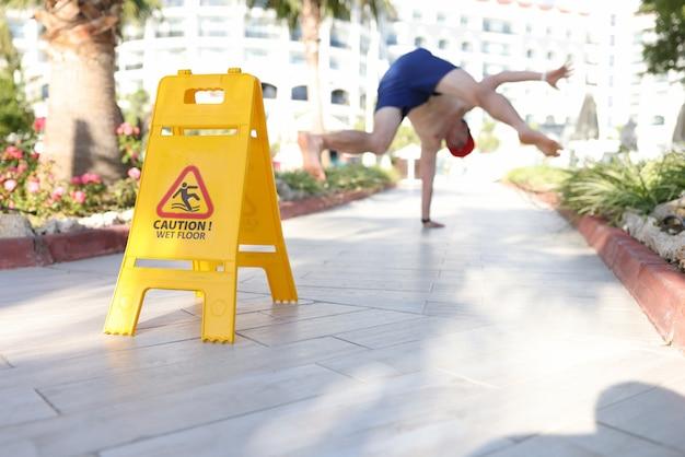 Segno giallo attenzione pavimento bagnato in piedi vicino al primo piano dell'uomo che cade