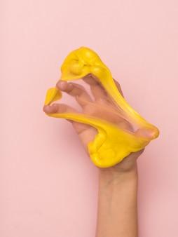 Melma gialla allungata sul palmo della mano su uno sfondo rosa. giocattolo antistress. giocattolo per lo sviluppo delle capacità motorie manuali.