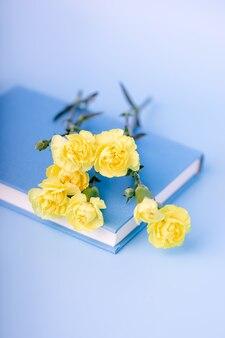 Piccoli fiori e libro gialli del garofano