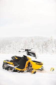 La motoslitta gialla è in piedi su un campo innevato sullo sfondo di un paesaggio panoramico invernale
