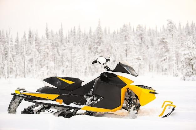 La motoslitta gialla è in piedi su un campo innevato all'aperto