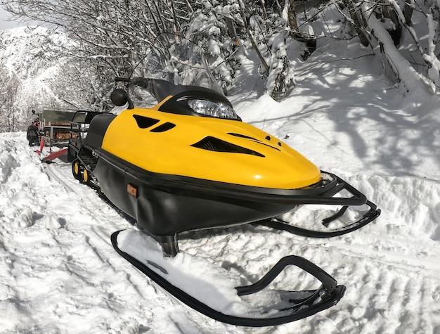 Motoslitta gialla sulla neve al giorno pieno di sole di inverno
