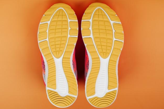 Suola gialla di una scarpa da tennis isolata sull'arancio