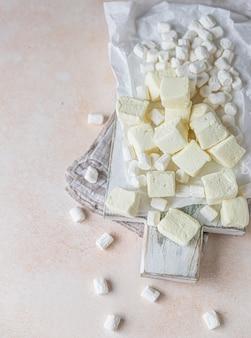 Marshmallow di forma quadrata gialla e marshmallow alla vaniglia bianca su tagliere di legno
