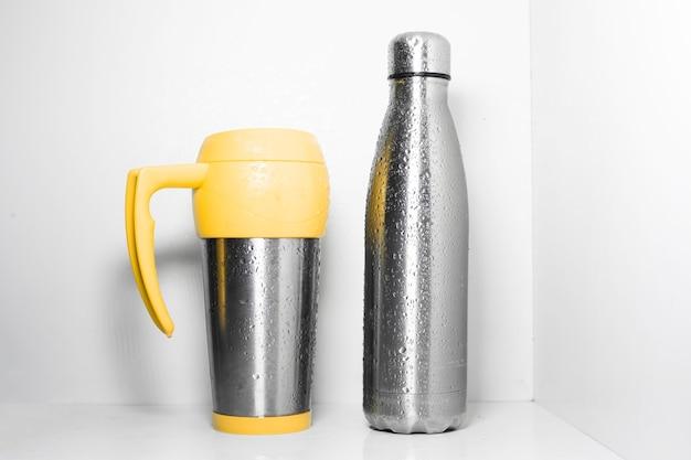 Tazza termica in acciaio giallo e bottiglia termica in acciaio inossidabile eco spruzzata con acqua su bianco.