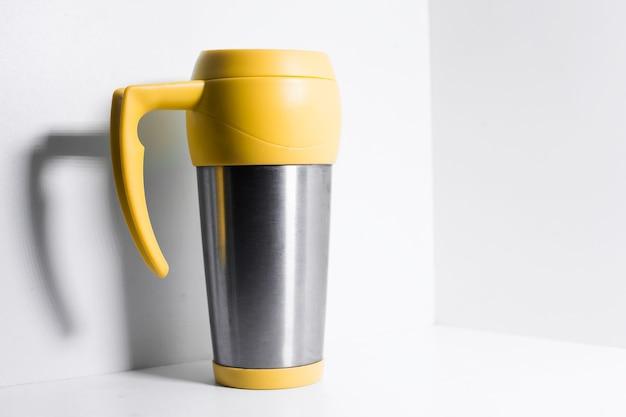 Tazza termica in acciaio giallo spruzzata con acqua su fondo bianco.