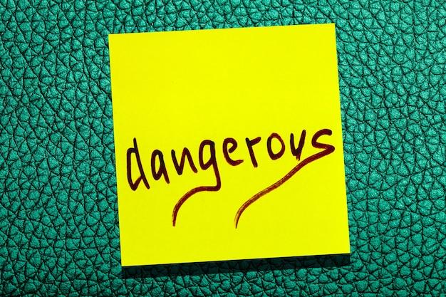 Foglia gialla appiccicosa sul muro. marcatore di iscrizione parola pericoloso