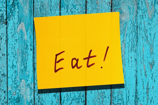 Foglia gialla appiccicosa sul muro. marcatore di iscrizione parola mangiare