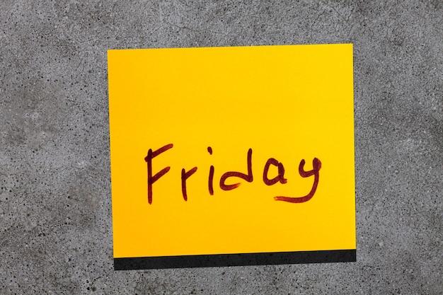 Foglia gialla appiccicosa sul muro. marcatore di iscrizione parola venerdì
