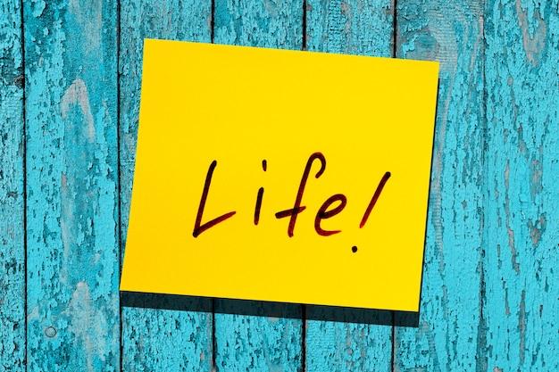 Foglia gialla appiccicosa sul muro. marcatore di iscrizione parola vita