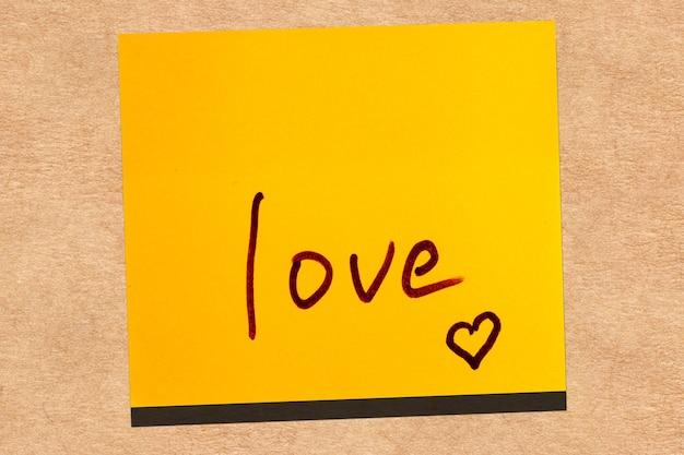 Foglia gialla appiccicosa sul muro. marcatore di iscrizione parola amore