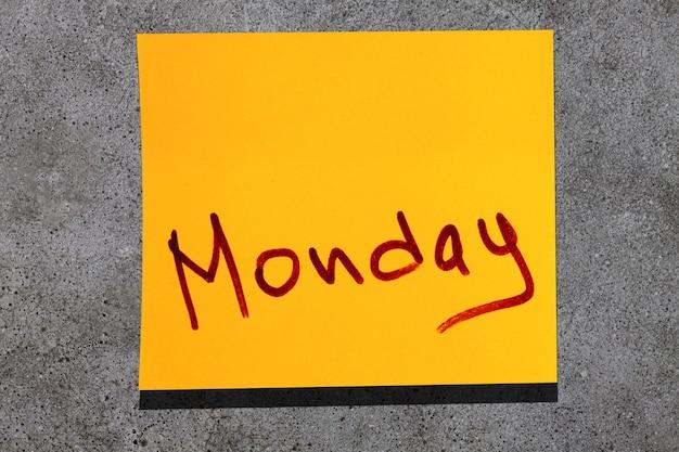 Foglia gialla appiccicosa sul muro. parola marcatore di iscrizione lunedì