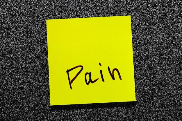 Foglia gialla appiccicosa sul muro. marcatore di iscrizione parola dolore