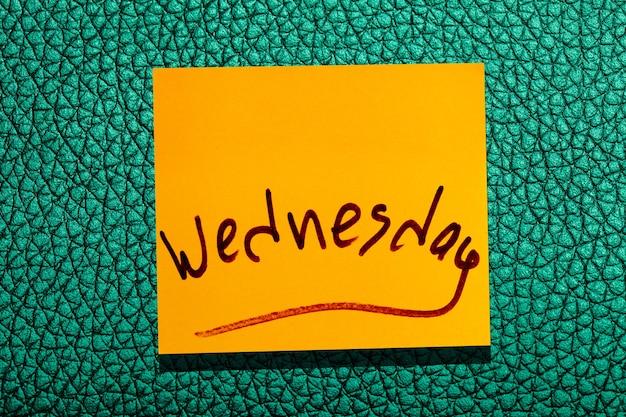 Foglia gialla appiccicosa sul muro. marcatore di iscrizione parola mercoledì
