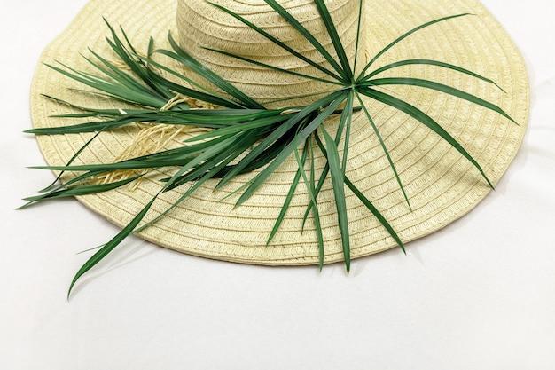 Cappello di paglia giallo con verdi su sfondo bianco