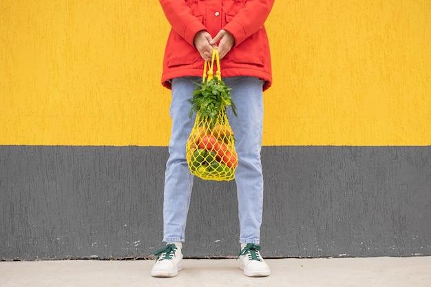 Borsa di corda gialla con cetrioli, pomodori, banane ed erbe nelle mani della ragazza in blue jeans, giacca rossa. foto luminosa nei toni del rosso, giallo e verde. sostenibilità, zero sprechi, concept plastic free.
