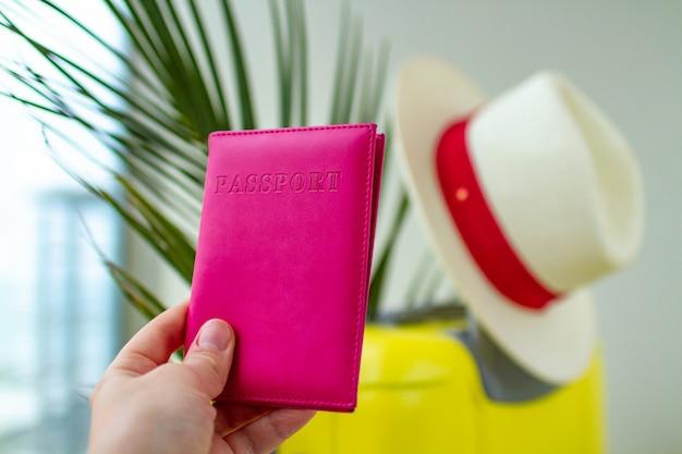Valigia gialla, cappello, passaporto turistico, ramo di palma