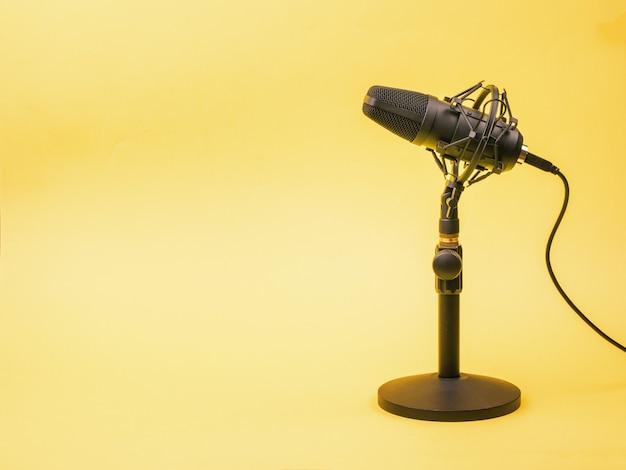 Una superficie gialla e un moderno microfono a condensatore