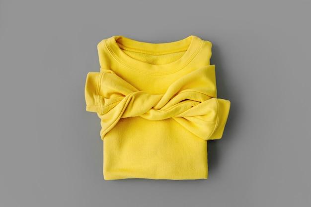 Maglione giallo su sfondo grigio. colori dell'anno 2021 ultimate grey e illuminating. eleganti vestiti autunnali o invernali da donna. disposizione piana, vista dall'alto.
