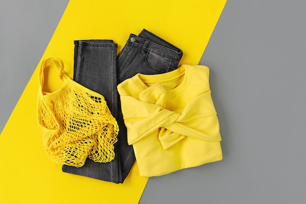 Maglione giallo, jeans e borsa a rete su sfondo grigio. colori dell'anno 2021 ultimate grey e illuminating. elegante set di vestiti autunnali o invernali da donna. disposizione piana, vista dall'alto.