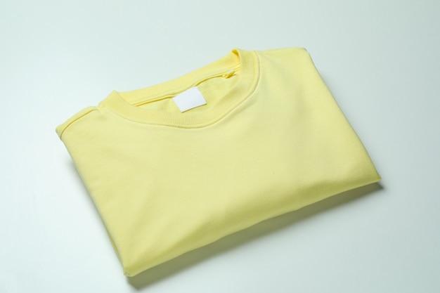 Felpa gialla su superficie bianca