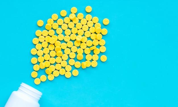 Compresse gialle di paracetamolo su fondo blu.