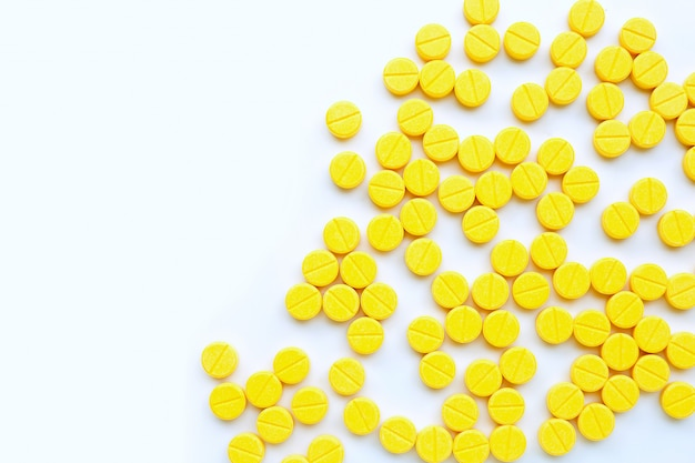 Compresse gialle di paracetamolo su fondo bianco.