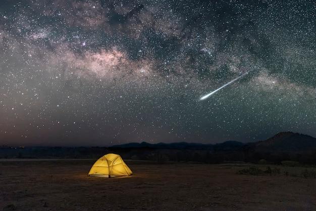 Tenda gialla sotto la via lattea con meteora nel deserto nella campagna del nord della thailandia, stelle sopra la foresta di montagna di notte e una tenda da campeggio luminosa.