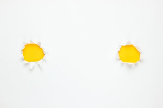Fori strappati gialli su carta bianca