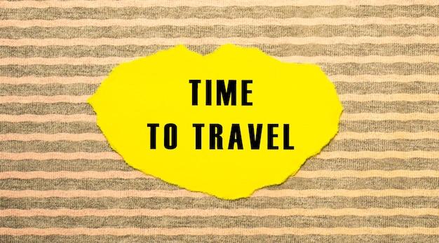 Carta strappata gialla con il testo time to travel su uno sfondo grigio rosa